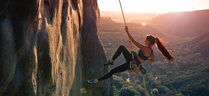 Image of woman climbing a rock face on a canyon wall for Quotacy blog Challenges Consumers Face with Life Insurance.