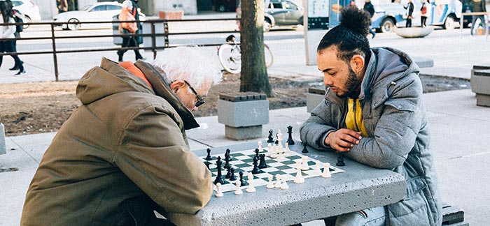 senior man and younger man playing chess outside in park