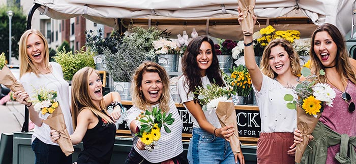 Image of happy women holding flower bouquets at a street cart for Quotacy blog Women's Need for Life Insurance.