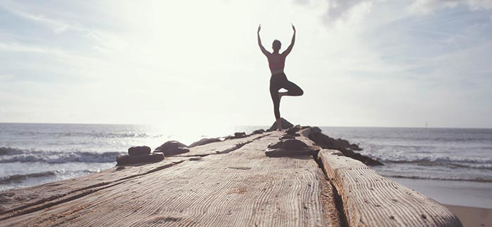Image of a woman doing a yoga pose on a log facing the ocean for Quotacy blog 7 Tips to Help Manage Stress.