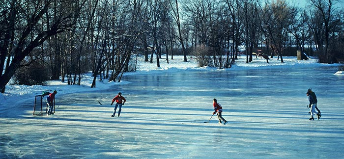 Image of kids playing ice hockey on a frozen lake in winter for Quotacy blog Embracing Winter.