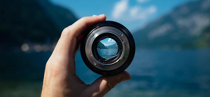 Image of camera lens focusing on mountain lake for Quotacy blog Things to Look for When Shopping Online for Life Insurance.
