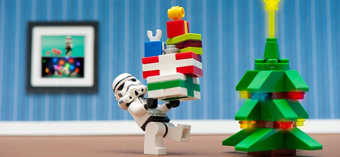 Image of lego stormtrooper putting gifts under a christmas tree for Quotacy blog How to Keep Holiday Spending Under Control.