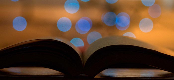 Image of an open book with blue light reflected in a window for Quotacy blog Things to Know When Considering Life Insurance.