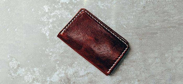Image of stitched brown leather wallet on concrete countertop for Quotacy blog What to Keep or Not to Keep in Your Wallet.