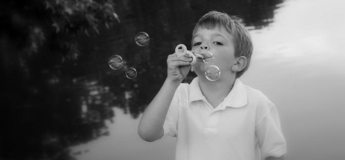 Image of little boy blowing bubbles in front of a pond for Quotacy blog Buying Life Insurance on Your Children.
