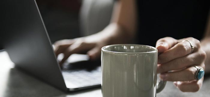 Image of woman with laptop reaching for coffee cup for Quotacy blog Buying Life Insurance Online Doesn't Mean It's Cheaper.
