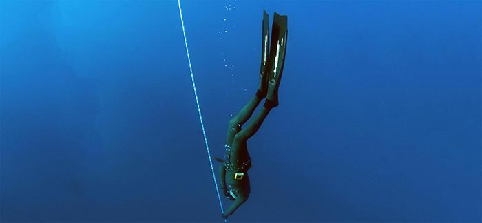Image of diver descending in the ocean with a rope for Quotacy blog Reasons Why Companies May Raise Your Life Insurance Costs
