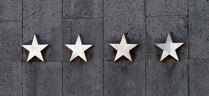 Image of four silver stars hanging on a building for Quotacy blog What You Need To Know About Life Insurance Company Ratings.