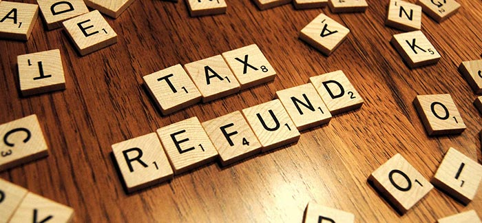 Image of scrabble board pieces spelling out tax refund for Quotacy blog 7 Great (and Smart) Ways to Spend Your Tax Refund.