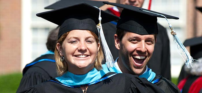 Image of two college graduates with smiling faces in their cap and gown.
