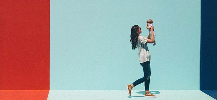 Image of mom walking and holding baby in the air for Quotacy blog Life Insurance for Moms.