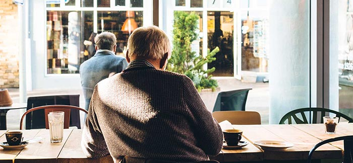 Image of retired man relaxing at a coffee shop for Quotacy blog 10 Reasons Why You May Need Life Insurance in Retirement.