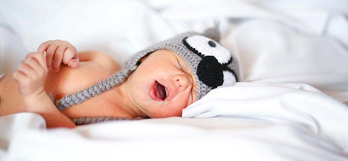 Image of sleeping newborn baby wearing a knitted animal hat for Quotacy blog Reasons Young Families Choose Term Insurance.