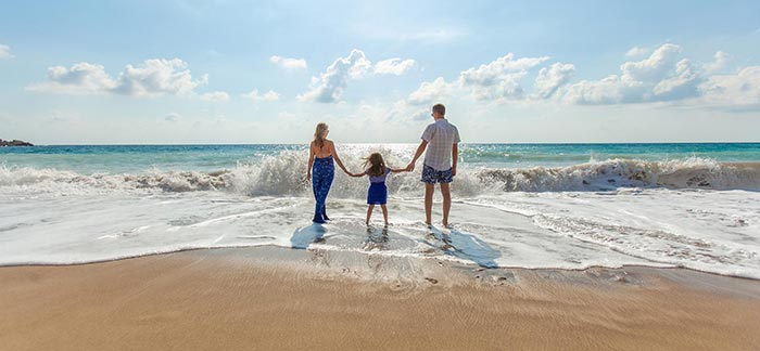 Image of mom, dad, and daughter holding hands in front of the ocean for Quotacy blog Balancing Your Work and Family Life.