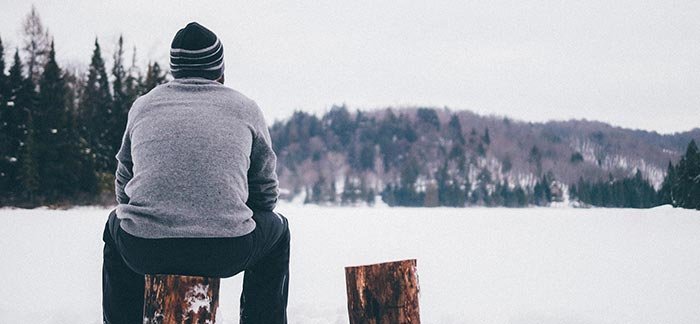Image of man sitting on stump looking at trees in winter for Quotacy blog Cholesterol Changes with the Seasons You Should Too
