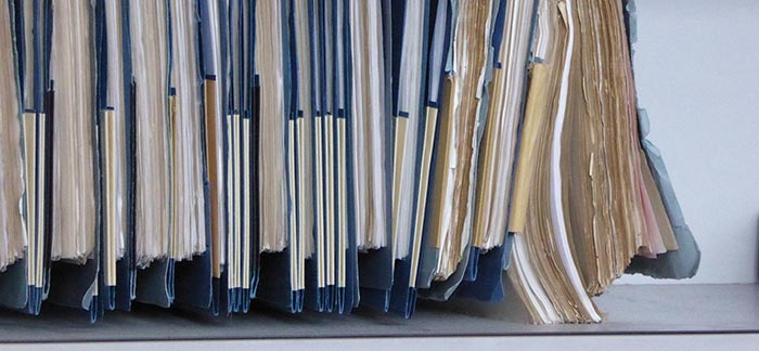 Image of hanging blue file folders filled with documents for Quotacy blog Completing Your Delivery Documents.