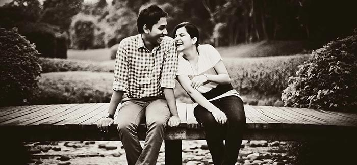 Image of two people laughing sitting closely on a dock for Quotacy blog Can Couples Get a Better Deal On Coverage?