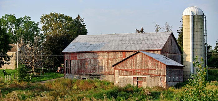 Image of farm with red wooden barn and silo for Quotacy blog Life Insurance and Estate Planning for Farm Owners.