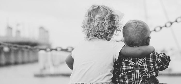 Image of little girl hugging her baby brother sitting on a dock for Quotacy blog Owning a Policy: Your Annual Check-Up.