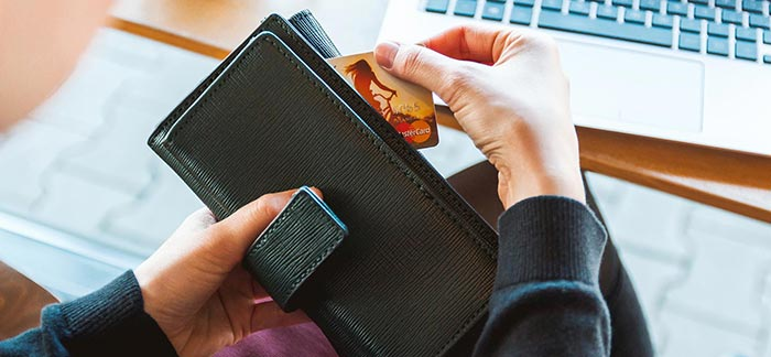 Image of woman opening wallet at desk to retrieve her credit card for Quotacy blog How to Make the Best of Your Finances.