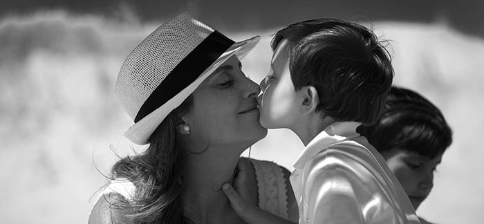 Image of a mother giving her child a kiss for the Quotacy blog, The Importance of Life Insurance for Single Parents.