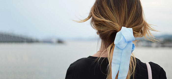 Image of woman wearing a blue ribbon standing on a beach for Quotacy blog Cervical Cancer and How It Affects Life Insurance.