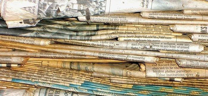 Image of stack of old newspapers for Quotacy newsletter Robot Doctors and Real Estate.