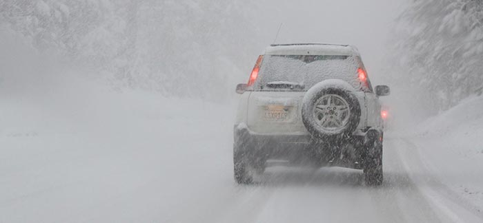 Image of a vehicle driving on snowy road in snowstorm for Quotacy blog Building a Winter Survival Car Kit.