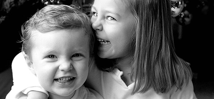 Image of big sister with arm around shoulder of her little brother for Quotacy blog What Is a Life Insurance Child Rider?