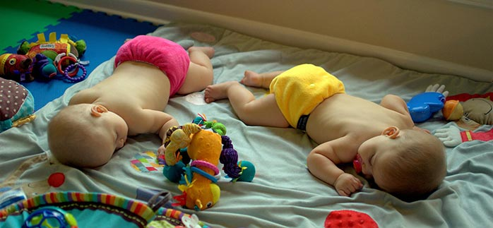 Image of twin babies sleeping next to baby toys for Quotacy blog The Right Amount of Sleep Is More Important Than You Think.