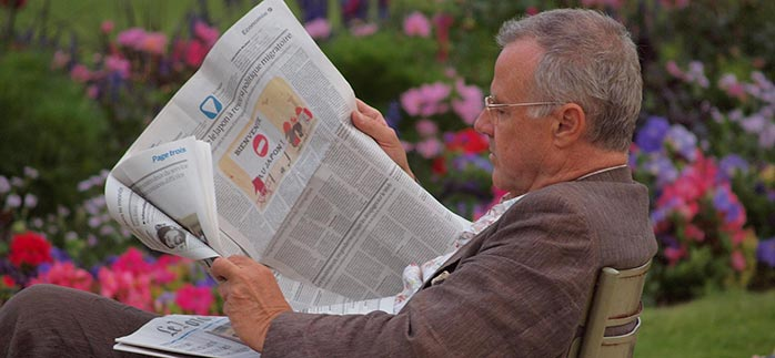 Image of man reading French newspaper in the park for Quotacy newsletter Clean Up Your Act This Spring.