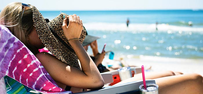 Image of woman covering her face to hide from the sun on a beach for Quotacy blog How to Enjoy Summer and Protect Your Skin.