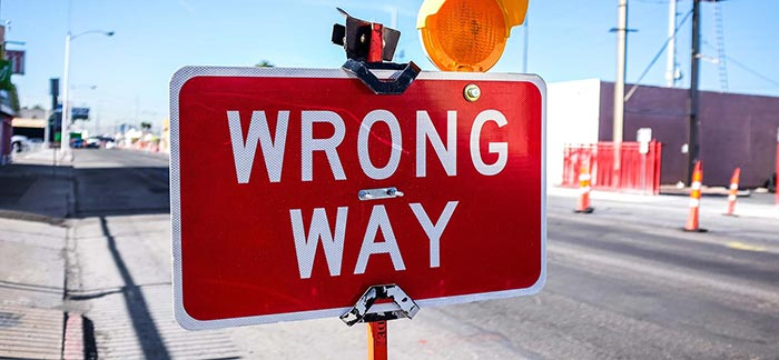 Image of wrong way sign on the side of road under construction for Quotacy blog 6 Things to Avoid When Buying Life Insurance