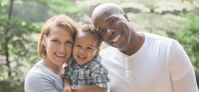 Image of couple holding their son smiling at the camera for Quotacy blog The Advantages of Life Insurance for Young Families.