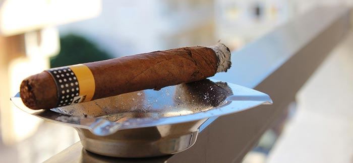 Image of lit cigar in ashtray for Quotacy blog Do Cigars Affect Life Insurance Rates?