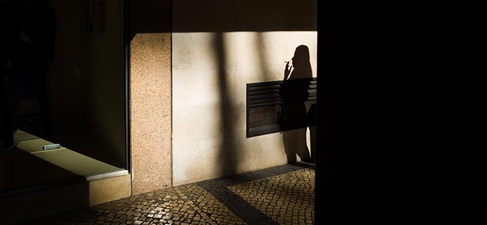 Image of shadow of person smoking a cigarette for Quotacy blog Life Insurance Risk Classes for Cigarette Smokers.