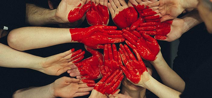 Image of several red painted hands held together to form a heart for Quotacy blog: Blood Cancers and Buying Life Insurance.