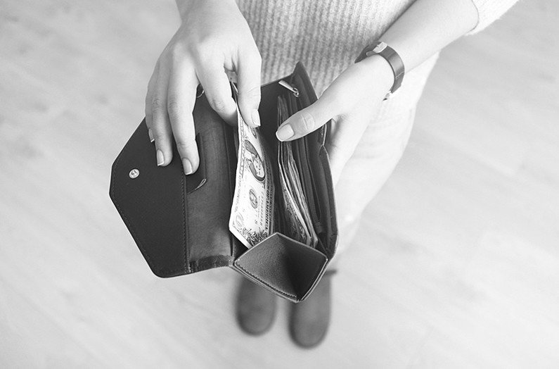 Image of woman counting the dollar bills in her wallet for Quotacy cover your debt.