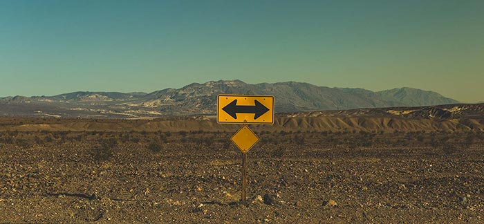 Image of desert road with left or right arrow sign for Quotacy blog: Life Insurance: How to Make the Best Decision for You.