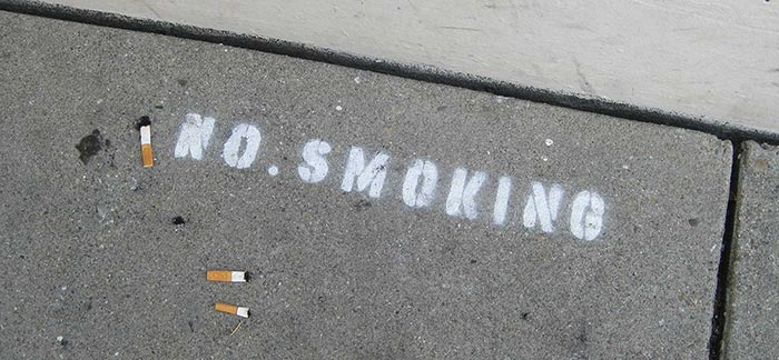 Image of spray-painted no smoking sign with three cigarette butts for Quotacy blog: Thinking About Quitting Smoking.