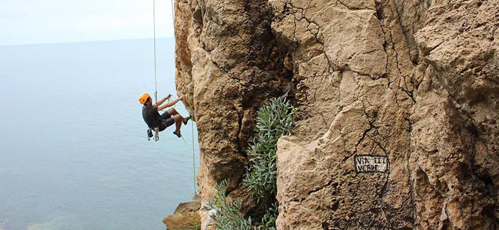 Image of man repelling dow a cliff over the ocean for Quotacy blog The Five Most Common Risky Hobbies That Underwriters See.