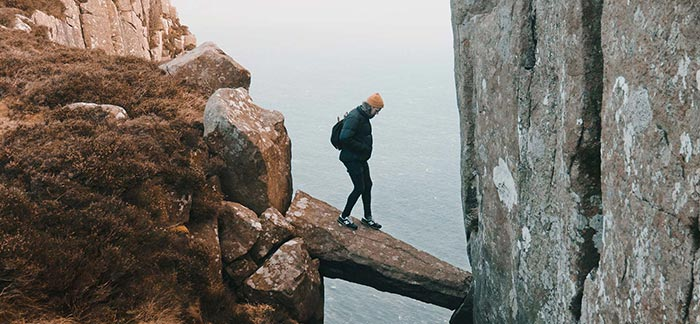 Man walking across stone ledge for Quotacy blog What Are the Life Insurance Risk Factors?