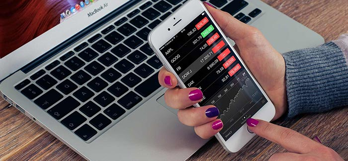 Woman checking stock market on her phone for Quotacy blog What the Raised Interest Rates Mean for You