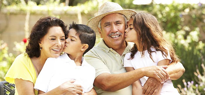 Image of grandma and grandpa hugging their grandchildren for the Quotacy blog: What Is Final Expense Life Insurance?