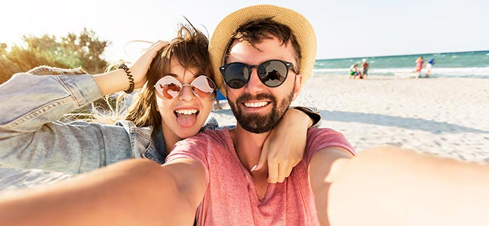 Image of young couple on beach for Quotacy blog on life insurance for digital nomads and travelers.