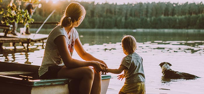 Image of woman sitting on a boat on the lake holding her toddler's land for Quotacy blog How Do Life Insurance Payouts Work?