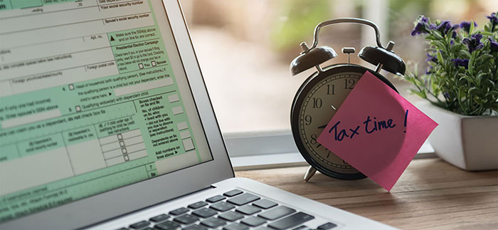 Image of clock with tax time post it note for Quotacy blog: Are Life Insurance Premiums Tax Deductible?
