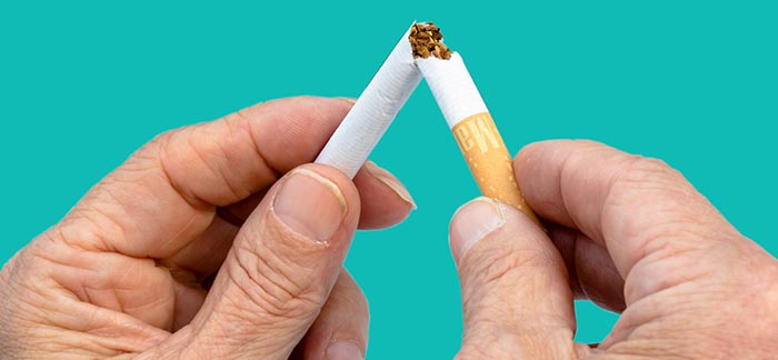 Image of two hands breaking a cigarette in half for Quotacy blog How Smoking Cessation Products Affect Life Insurance Rates