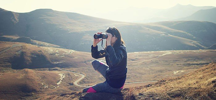 Image of woman sitting on hillside with binoculars for Quotacy blog Can Someone Buy Life Insurance on Me Without My Consent?